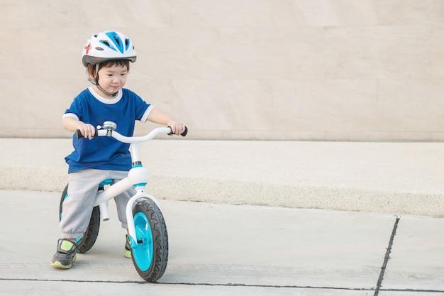 El niño lindo del primer monta una bicicleta en piso del cemento en el aparcamiento