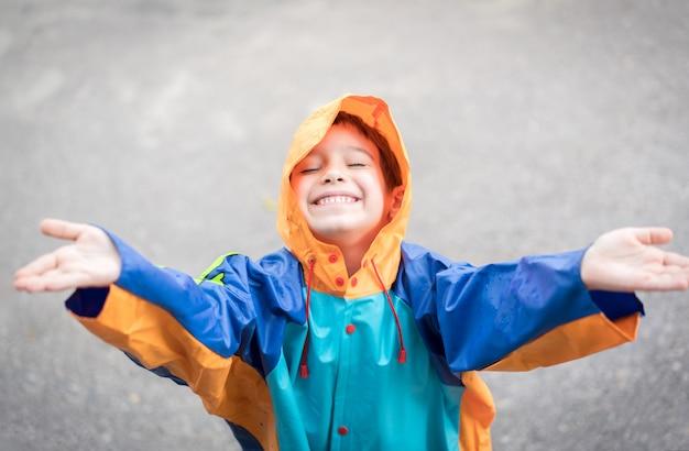 Niño lindo para probar la lluvia