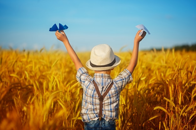 Niño lindo que camina en el campo de oro del trigo en un día de verano soleado. el muchacho comienza el avión de papel. naturaleza en el campo. vista posterior.