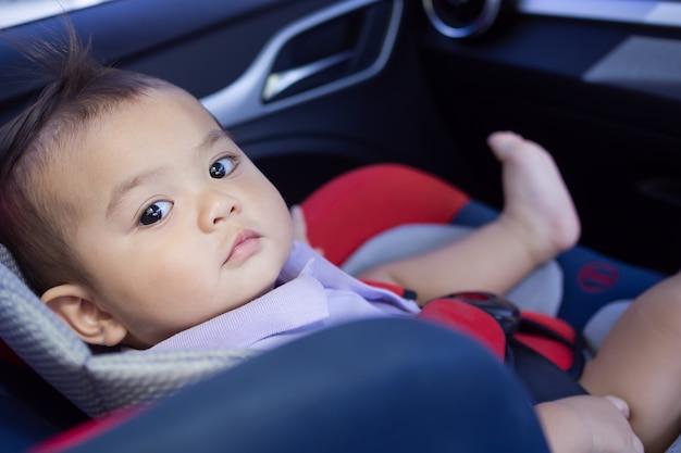 El niño lindo que se sienta en el coche se sienta en el coche.