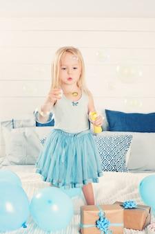 Niño lindo que sopla burbujas. niña en casa. vacaciones para niños