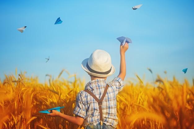 Niño lindo que sostiene el aeroplano de papel disponible en el campo de oro del trigo en un día de verano soleado.