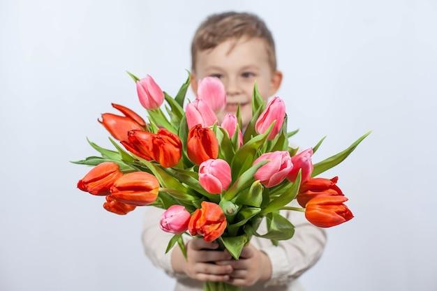 Niño lindo con un ramo de flores. tulipanes día de la madre. día internacional de la mujer. retrato de un niño feliz en una pared blanca. primavera.