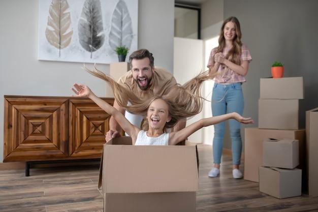 Niño lindo sentado en una caja y divirtiéndose con papá