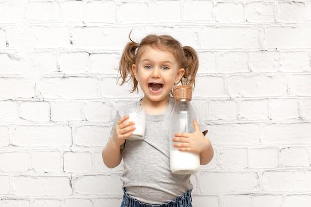 Niño lindo sorprendido con cara de expresión y bigote de leche en los labios sobre pared de ladrillo blanco