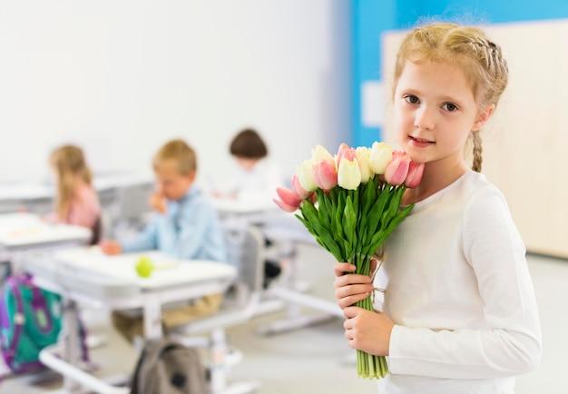 Niño lindo sosteniendo un ramo de flores
