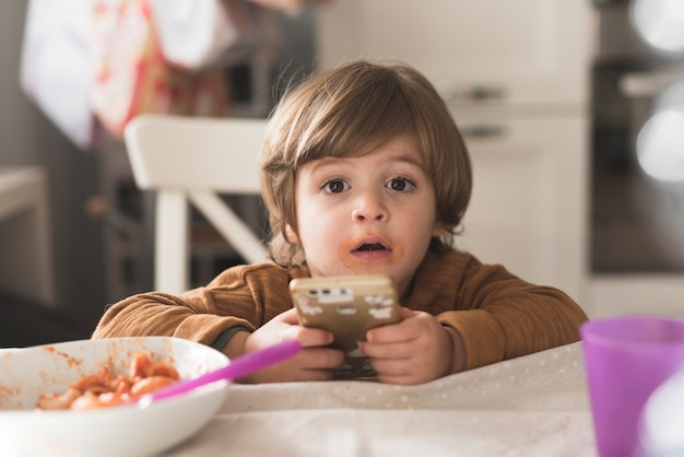 Niño lindo con teléfono en la mesa
