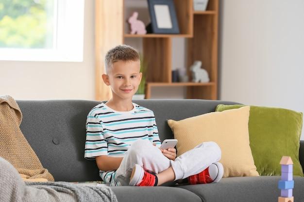 Niño lindo con teléfono móvil en casa