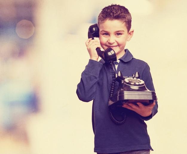 Niño lindo con un teléfono vintage