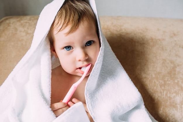 Niño lindo en toalla blanca grande que se cepilla los dientes con cepillo de dientes