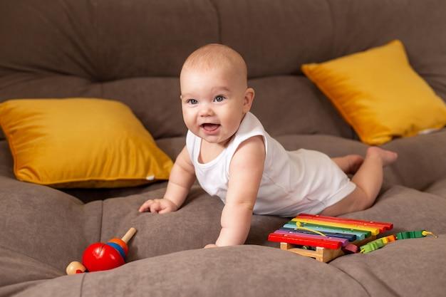 Niño lindo en traje blanco se encuentra en casa en un sofá gris con almohadas amarillas jugando con juguete de madera en desarrollo
