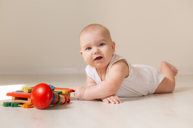 Niño lindo en traje blanco se encuentra en el piso de madera de la casa con un juguete en desarrollo