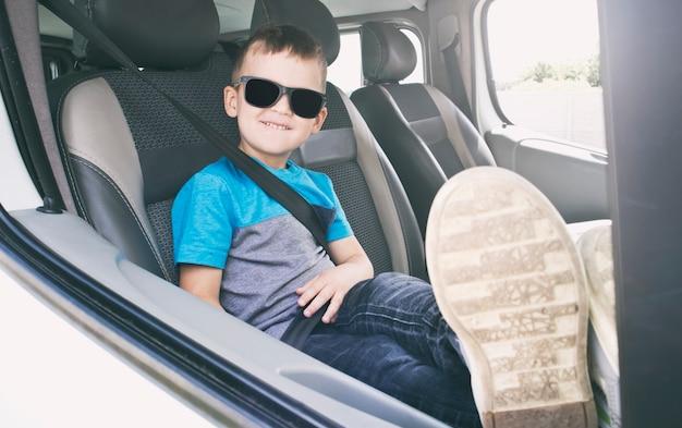 El niño está listo para las aventuras. el niño está sentado en el auto con gafas de sol.