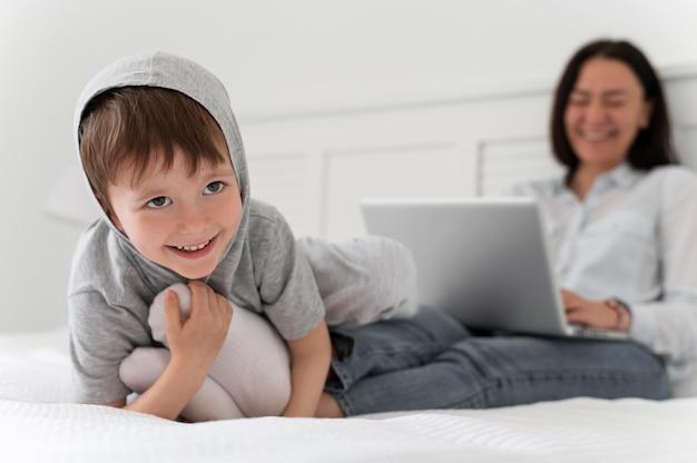 Niño y madre borrosa de tiro completo en la cama