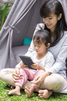 Niño y madre usando tableta mientras juegan en el patio de su casa