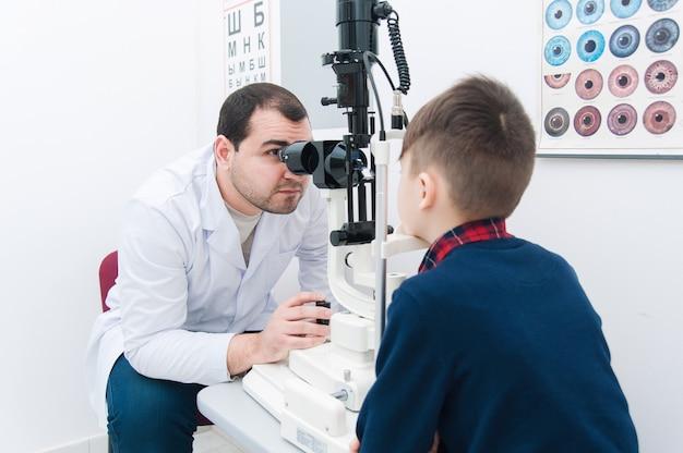 Niño con mamá en examen ocular por oftalmólogo