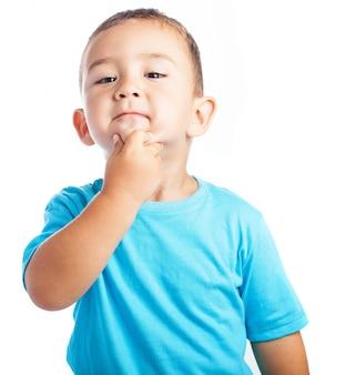 Niño con la mano en la barbilla