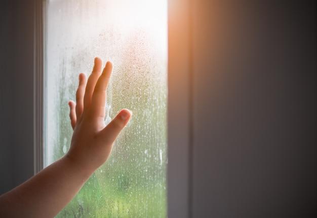 Niño de la mano con empañado en la ventana.