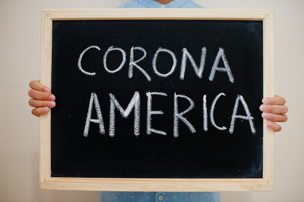 Niño mantenga inscripción en el tablero con el texto corona america
