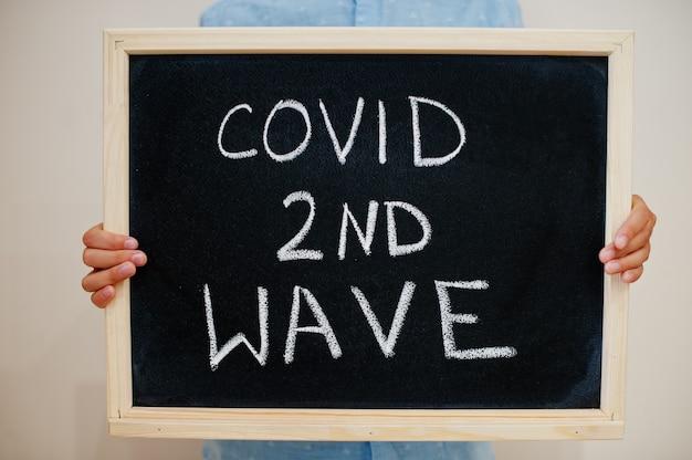 Niño mantenga inscripción en el tablero con el texto covid 2nd wave