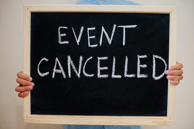 Niño mantenga inscripción en el tablero con el texto evento cancelado