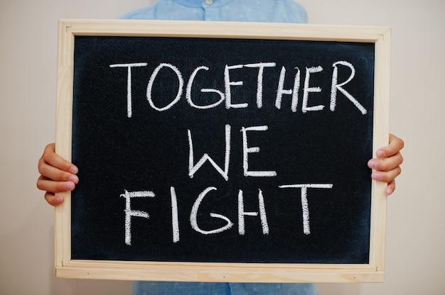 Niño mantenga inscripción en el tablero con el texto juntos luchamos