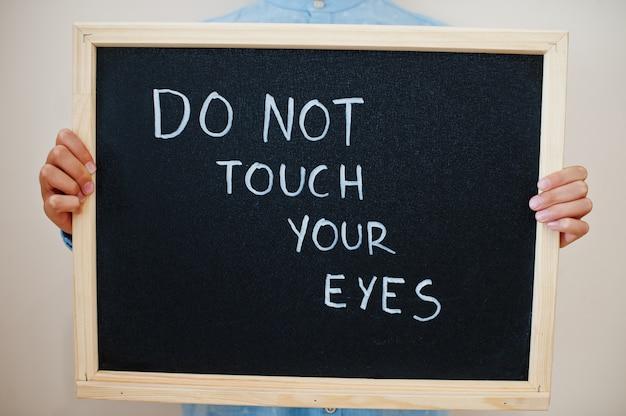 Niño mantenga la inscripción en el tablero con el texto no toque sus ojos