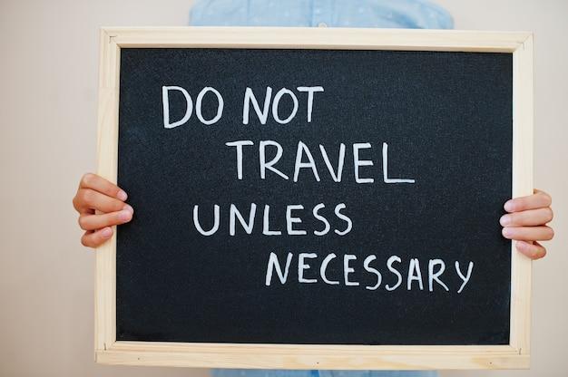 Niño mantenga inscripción en el tablero con el texto no viaje a menos que sea necesario