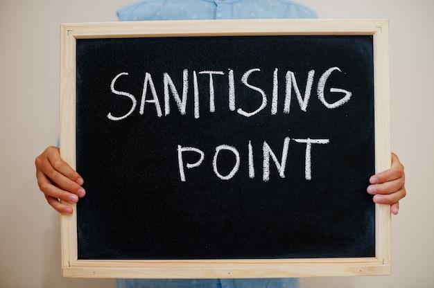 Niño mantenga inscripción en el tablero con el texto punto de desinfección