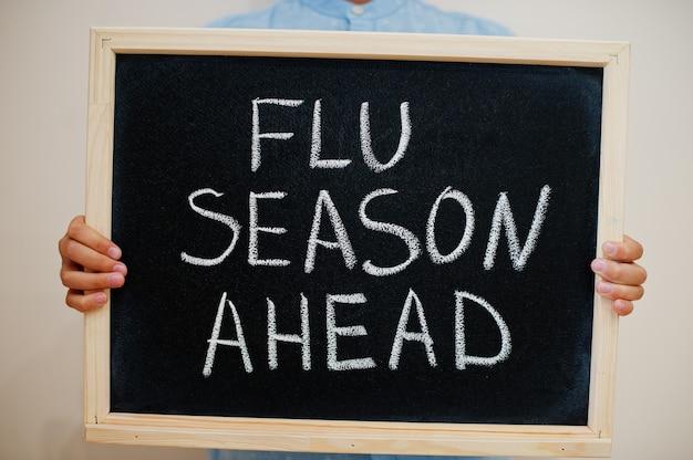 Niño mantenga inscripción en el tablero con el texto temporada de gripe por delante