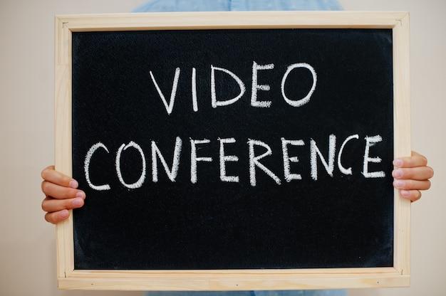 Niño mantenga inscripción en el tablero con el texto videoconferencia