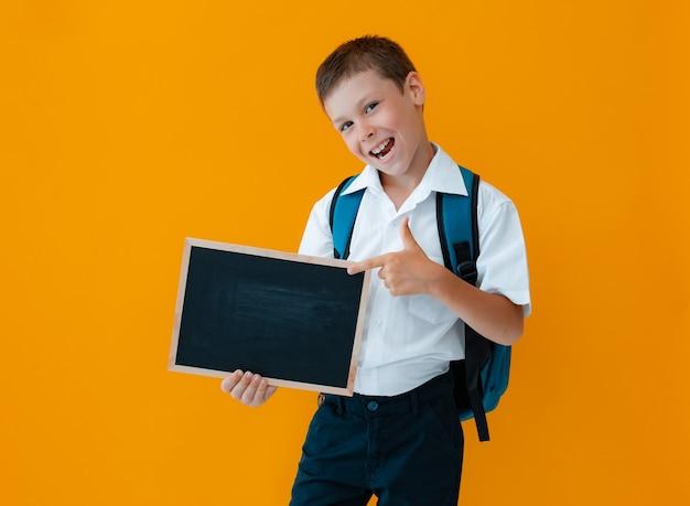 Niño mantenga la pizarra de la escuela sobre fondo amarillo. pequeño uniforme escolar escolar con una mochila con las manos en blanco. pizarra para anuncio, espacio de copia. para tu atención.