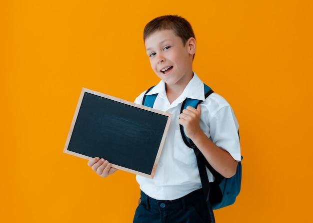Niño mantenga la pizarra de la escuela sobre fondo amarillo. pequeño uniforme escolar escolar con una mochila con las manos en blanco.