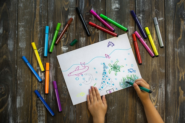 Niño de mar dibuja con lápices de colores.
