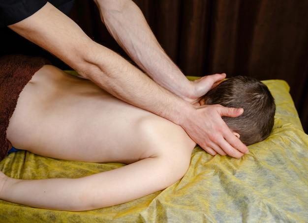 Niño con masaje de espalda en un centro de rehabilitación infantil. masajista masajeando a un niño