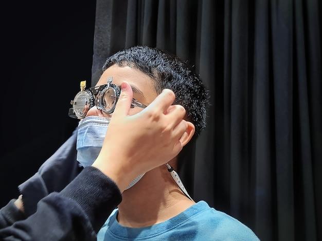 Niño con máscara y anteojos durante el examen ocular