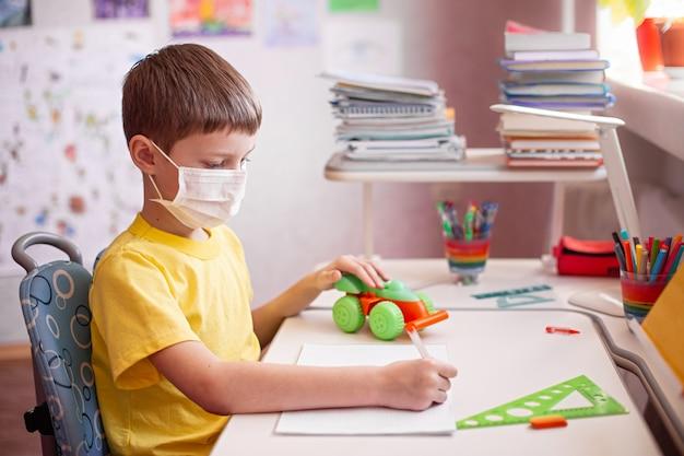 Niño con máscara haciendo la tarea y juega con su juguete favorito en casa