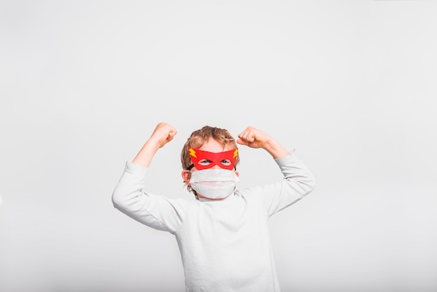 Niño con máscara de hospital, enfermo de virus, vestido de superhéroe, concepto de fuerza y esperanza.