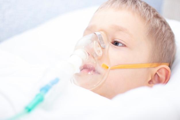 Niño con una máscara de inhalador en la cama