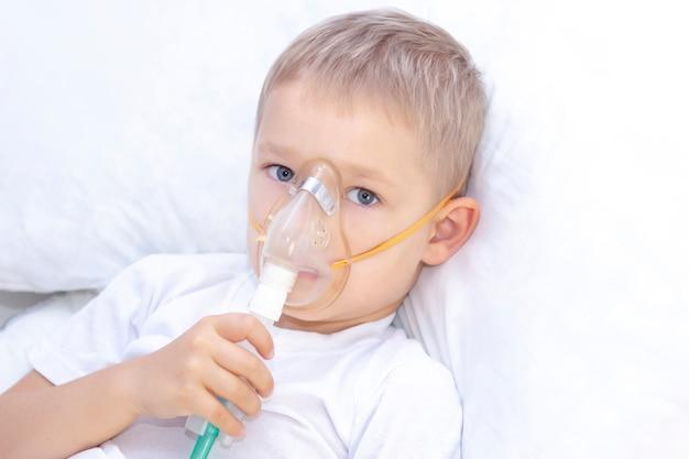 Niño con una máscara de inhalador - problemas respiratorios en el asma. un niño con una máscara inhaladora yace en la cama y respira adrenalina.