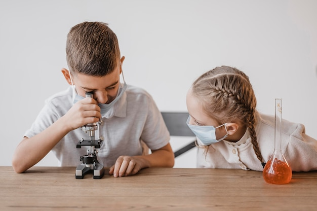 Niño con máscara médica mirando a través de un microscopio