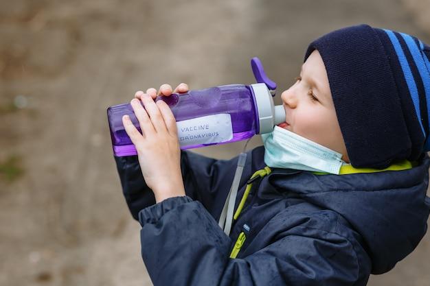 Un niño con una máscara médica que bebe agua de una botella que dice vacuna contra el coronavirus