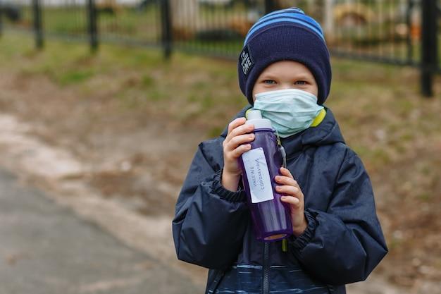 Un niño en una máscara médica sostiene un frasco con la vacuna de inscripción coronavirus