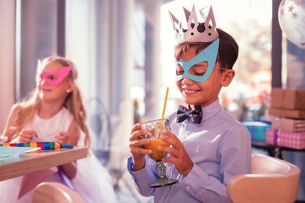 Niño con máscara de papel y sonriendo en una fiesta de cumpleaños