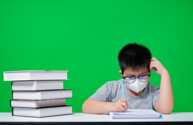 Niño con máscara de protección y haciendo la tarea en la pantalla verde, papel de escribir infantil, concepto de educación, regreso a la escuela