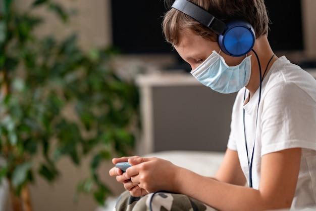 Niño con una máscara protectora y auriculares, con un teléfono inteligente en sus manos, vista lateral.