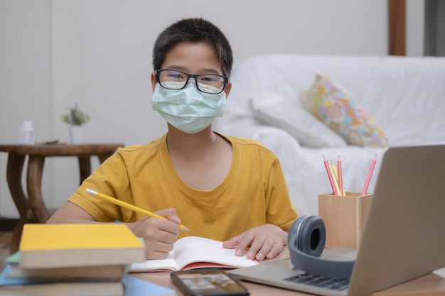 Niño con mascarillas estudiando en casa