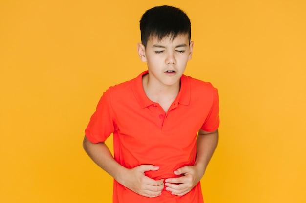 Niño mediano tiro que tiene un dolor de estómago