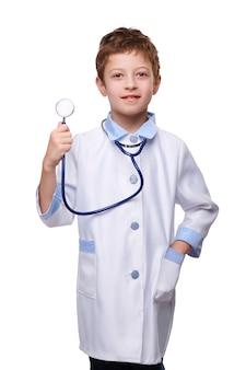 Niño médico en bata médica con estetoscopio sobre fondo blanco aislado