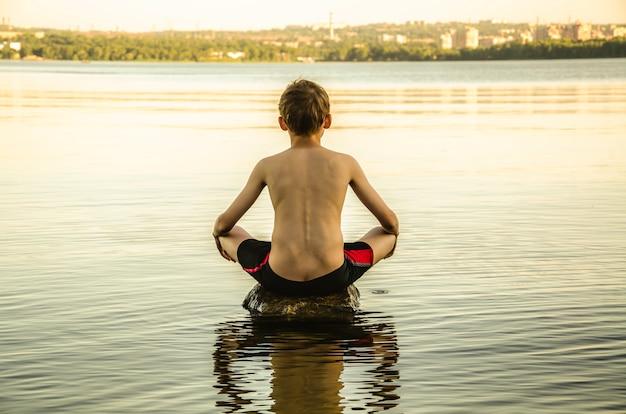 El niño está meditando en el río.